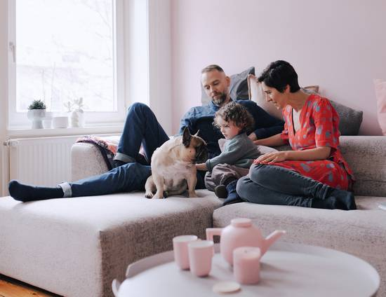 Couple sitting on a sofa with a small child and a pug.