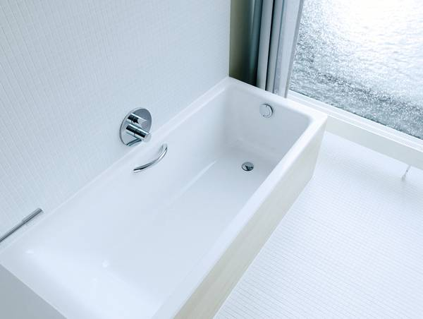 A white bathtub from above, a white floor and a floor-level window.