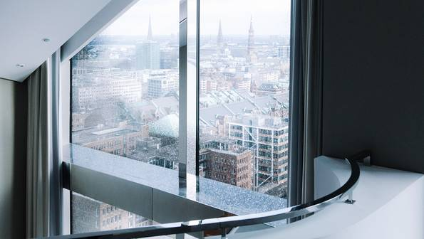 Five different views from the windows of the Westin Hotel Elbphilharmonie: from a gallery, close-up of a wave detail, looking down at a white sofa in front of a floor-level window, a view of the Elbe river, view from the bathtub into the hotel room.
