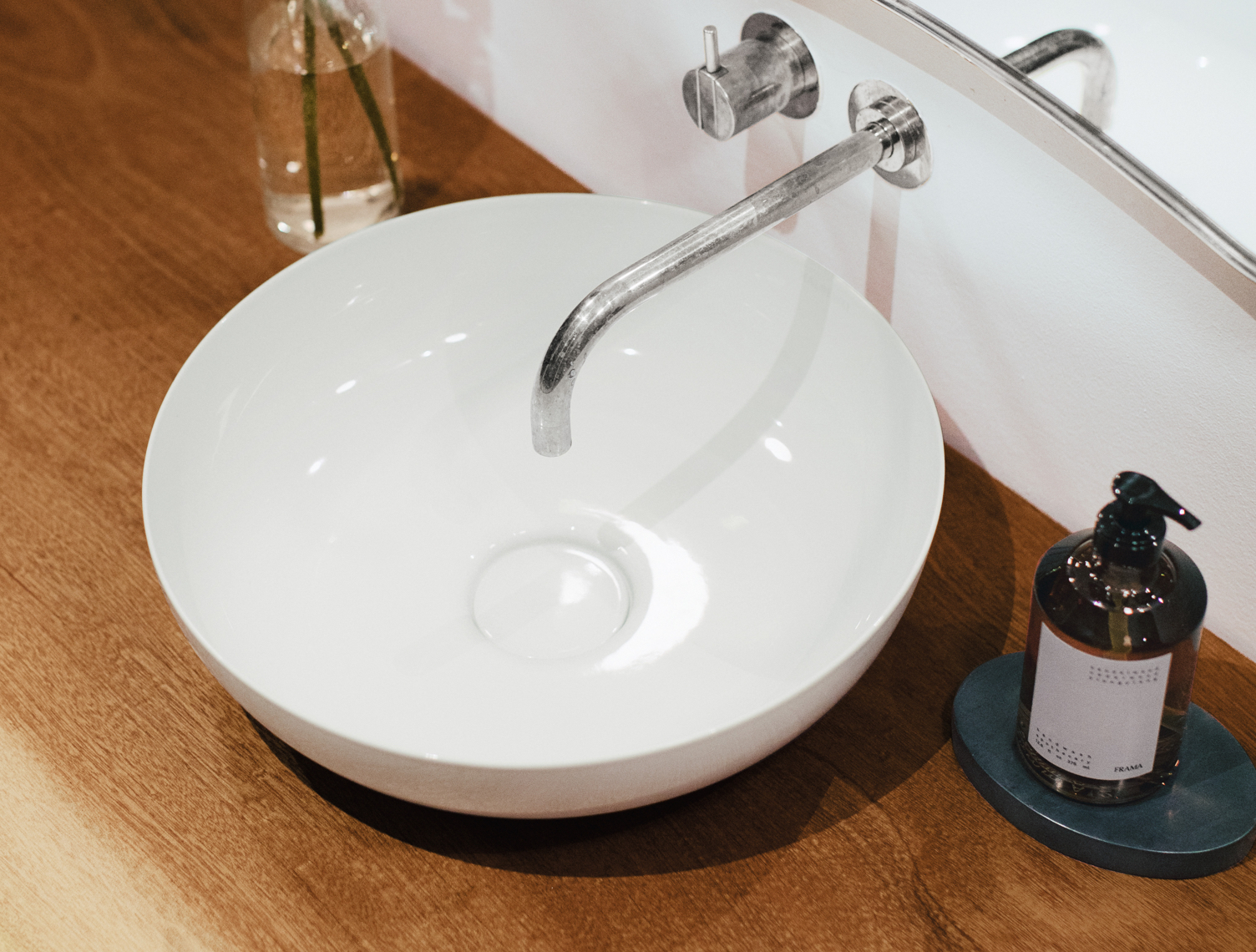 Using wood in the bathroom: a circular enamelled steel washbasin on an oiled wood surface.